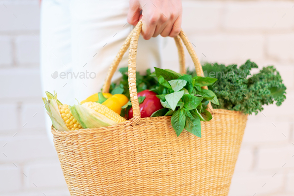 Zero waste concept with copy space. Woman holding straw basket with vegetables, products. Eco - Stock Photo - Images