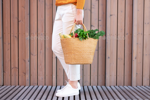Young girl holding straw basket with vegetables, products without plastic bags, wooden background - Stock Photo - Images