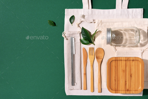 Cotton bags, glass jar, bottle, metal cup, straws for drinking, bamboo cutlery and boxes on green - Stock Photo - Images