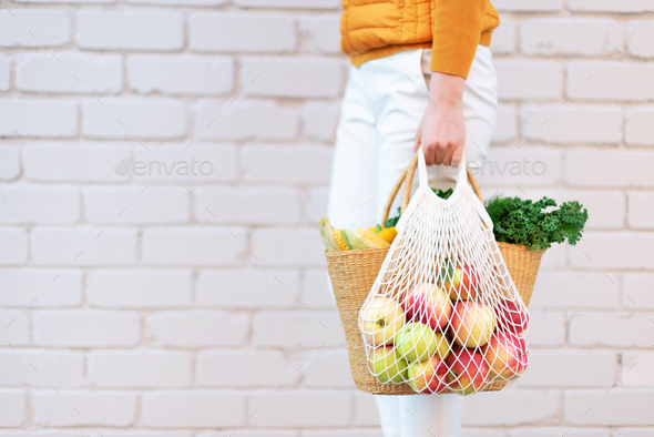 Zero waste concept with copy space. Woman holding straw basket and reusable mesh shopping bag - Stock Photo - Images
