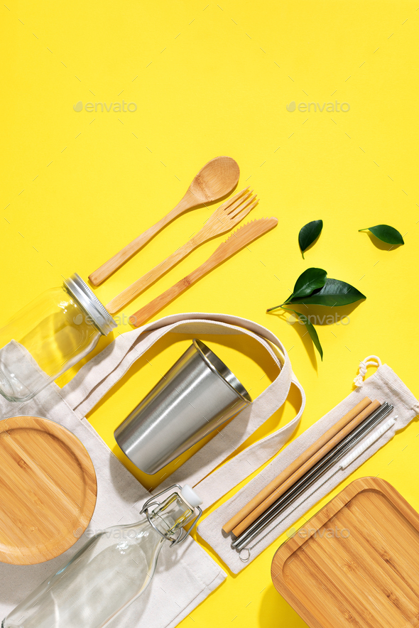 Cotton bags, glass jar, bottle, metal cup, straws for drinking, bamboo cutlery and boxes on yellow - Stock Photo - Images