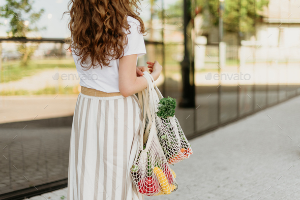 Girl holding mesh shopping bag and cotton shopper with vegetables without plastic bags, wooden - Stock Photo - Images