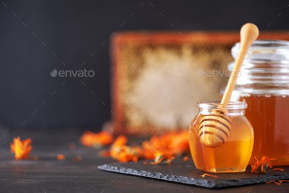 Herbal honey in jar with dipper, honeycomb, bee pollen granules, calendula flowers on black - Stock Photo - Images