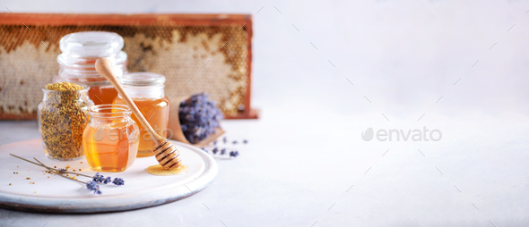 Bee pollen granules, honey jar with wooden dropper, honeycomb on grey backdrop. Copy space. Autumn - Stock Photo - Images