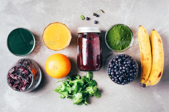 Blueberries, bilberry, barley grass, spirulina, orange juice, dulse, cilantro on marble background - Stock Photo - Images