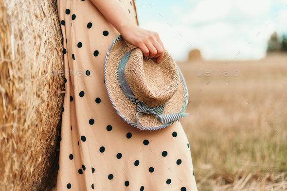 Young woman holding straw hat in wheat field. Agriculture background with copy space. Summer and - Stock Photo - Images