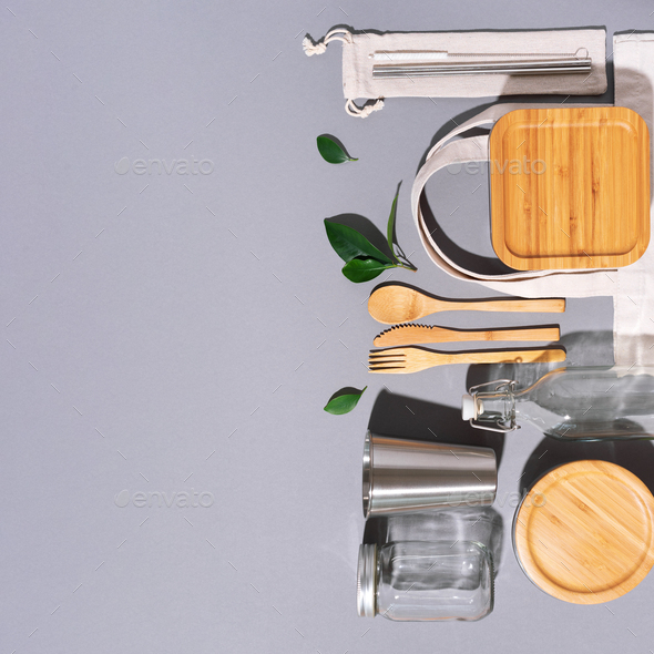 Cotton bags, glass jar, bottle, metal cup, straws for drinking, bamboo cutlery and boxes on gray - Stock Photo - Images