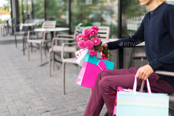 Boyfriend waiting for his girlfriend near cafe and holding flowers bouquet and bunch of pink gift - Stock Photo - Images