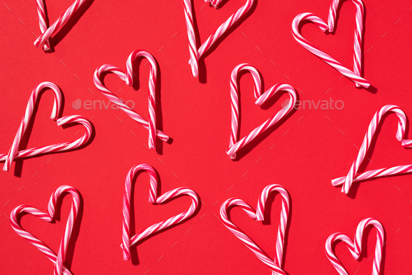 Pattern with hearts made of Christmas candy canes on red background. Top view. Flat lay. Love - Stock Photo - Images