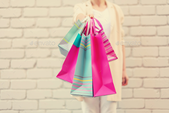Stylish girl in white clothes holding pink shopping bags. Sale, discount, black friday concept - Stock Photo - Images