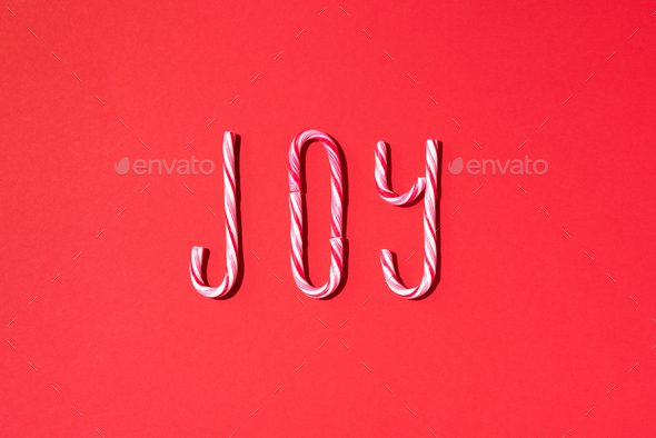 Joy word written with Christmas candy canes on red background. Top view. Flat lay. New year and - Stock Photo - Images