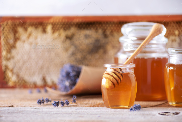 Herbal honey with lavender flowers, bee pollen granules, honey conb on grey background. Autumn - Stock Photo - Images