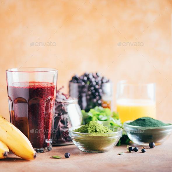 Fresh blueberries, bilberry, barley grass, spirulina powder, orange juice, dulse, cilantro on marble - Stock Photo - Images
