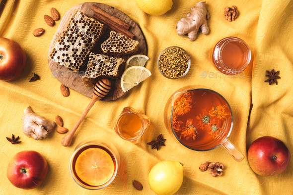Autumn harvest concept. Set of honey and bee products, apple, lemon, calendula tea, spices on yellow - Stock Photo - Images