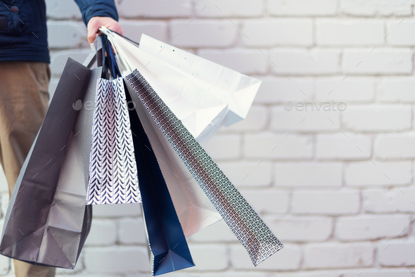 Male hand holding bunch of shopping bags with purchases near brick background. Copy space. Sale - Stock Photo - Images