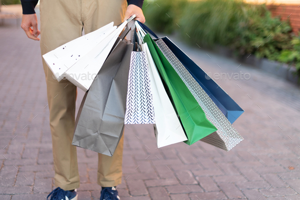 Man with bunch of shopping bags. Copy space. Sale, discount, black friday concept. Shopping mall and - Stock Photo - Images