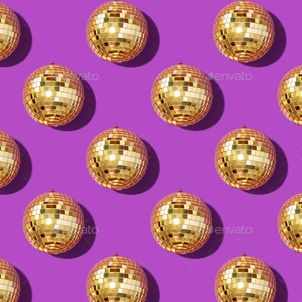 New year baubles. Shiny gold disco balls on violet background. Pop disco style attributes, retro - Stock Photo - Images
