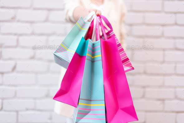 Pink flowers in female hands and shopping bags on brick background. Birthday, Mother's, Women - Stock Photo - Images