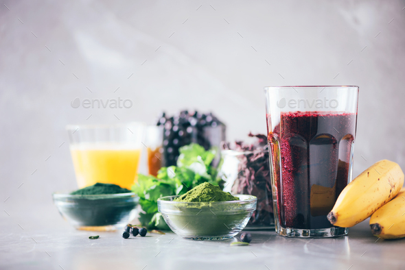 Healthy eating, alkaline diet, vegan concept. Blueberries, bilberry, barley grass juice, spirulina - Stock Photo - Images