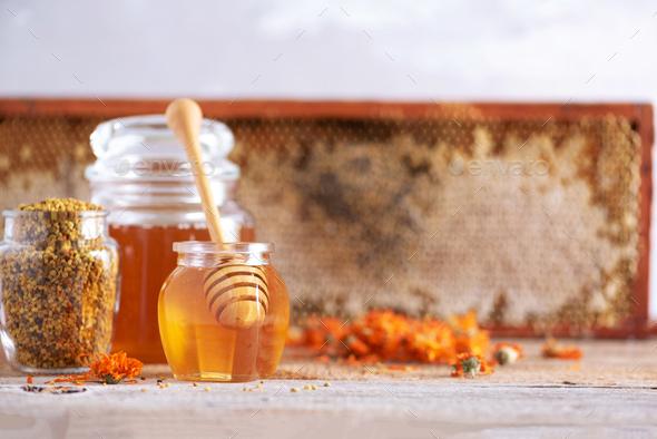 Herbal honey in jar with dipper, honeycomb, bee pollen granules, calendula flowers on grey - Stock Photo - Images