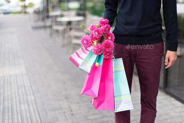 Stylish man holding flowers and pink, blue shopping bags near restaurant. Woman's day. Valentine - Stock Photo - Images