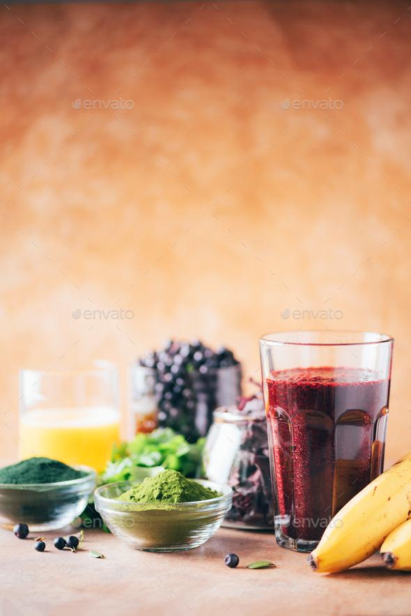 Healthy eating, alkaline diet, vegan concept. Blueberries, bilberry, barley grass, spirulina powder - Stock Photo - Images