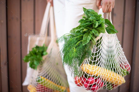 Zero waste concept with copy space. Woman holding cotton shopper and reusable mesh shopping bags - Stock Photo - Images
