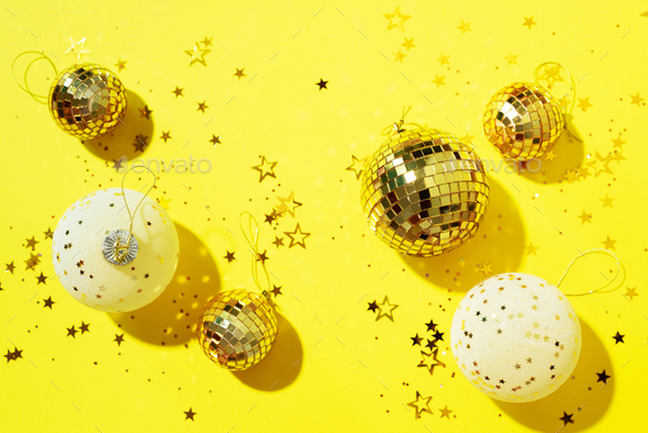 Christmas white and gold decorations, mirror disco balls, star sparkles over yellow background. Flat - Stock Photo - Images