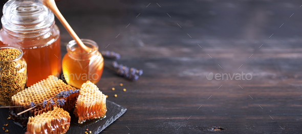 Bee pollen granules, honey jar with wooden dropper, honeycomb on dark backdrop. Copy space. Autumn - Stock Photo - Images