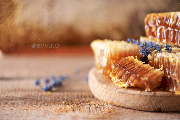 Fresh honeycombs pieces, dry lavender flowers on wooden background. Autumn harvest concept - Stock Photo - Images