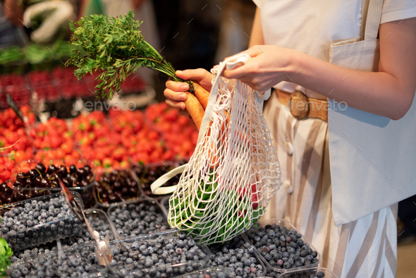 Zero waste, plastic free concept. Sustainable lifestyle. Woman chooses fruits and vegetables at - Stock Photo - Images