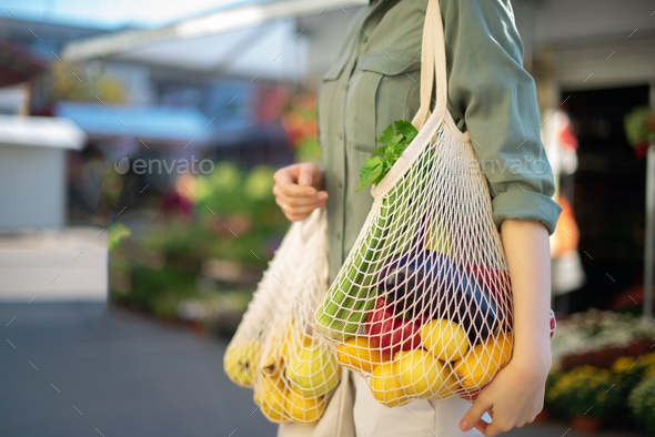 Girl holding mesh shopping bag and cotton shopper with vegetables without plastic bags at farmers - Stock Photo - Images