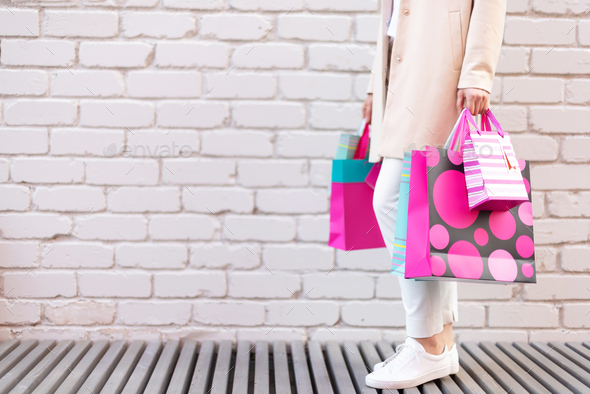 Shopping concept. Girl holding bunch of shopping bags with purchases near brick background. Copy - Stock Photo - Images