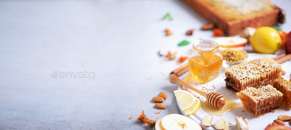 Ingredients for healthy hot drink. Lemon, ginger, mint, honey, apple and spices on grey concrete - Stock Photo - Images