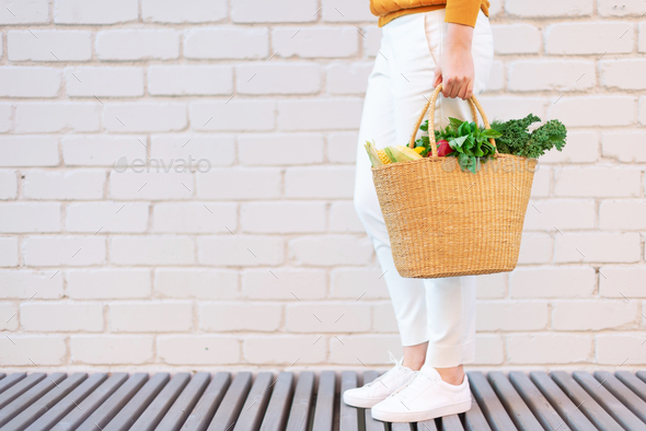 Young girl holding straw basket with vegetables, products without plastic bags, brick background - Stock Photo - Images