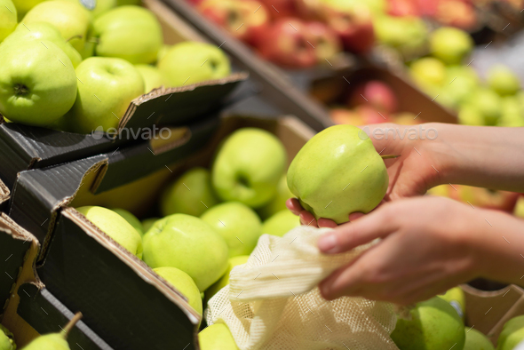 Woman chooses green apples at farmers market. Zero waste, plastic free concept. Sustainable - Stock Photo - Images