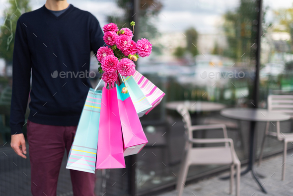 Romantic man giving flowers bouquet and bunch of pink gift bags near cafe. Ready for birthday party - Stock Photo - Images