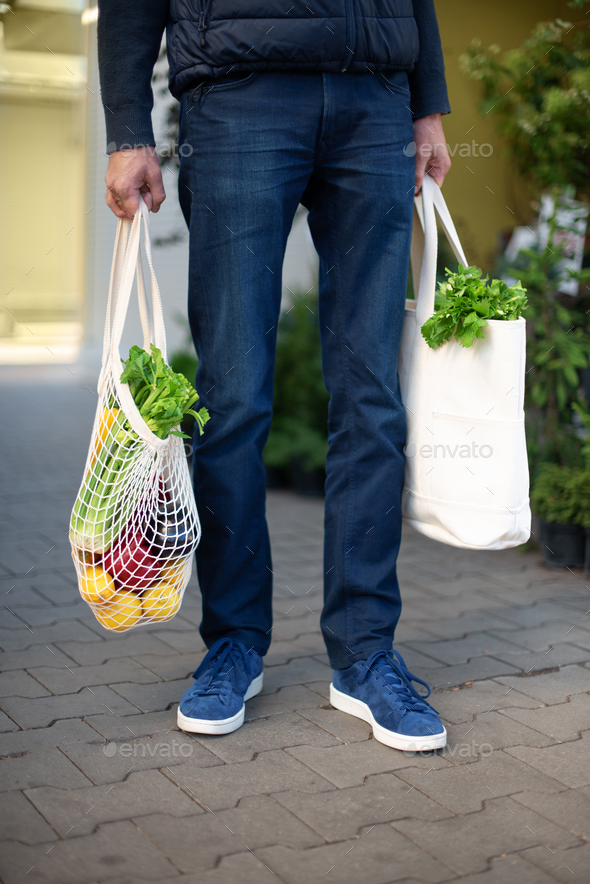 Zero waste concept with copy space. Young man holding cotton shopping bag with vegetables, products - Stock Photo - Images