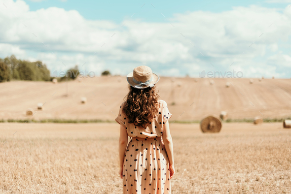 Girl in polka dot dress with curly hair, straw hat walking in field. Thanksgiving day, autumn - Stock Photo - Images