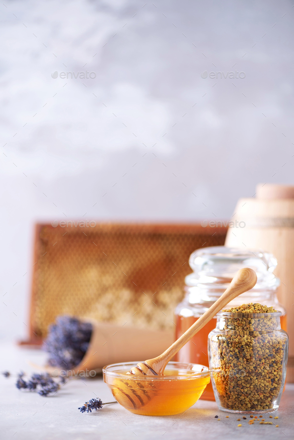 Honey products background. Honeycomb frame, bee pollen granules, honey in glass pot on grey concrete - Stock Photo - Images