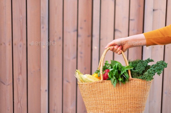 Woman hand holding straw basket with organic vegetables over wooden background. Healthy food - Stock Photo - Images