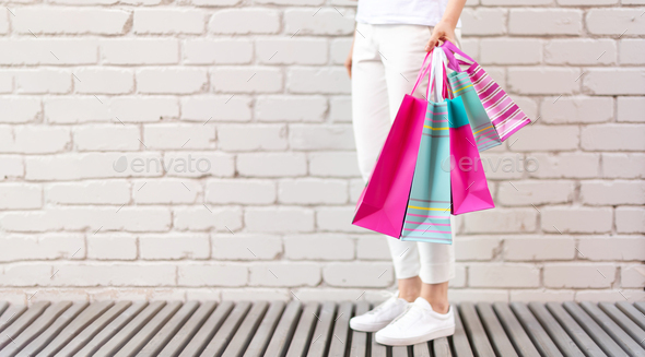 Female hands holding flowers and shopping bags on brick background. Woman's day. Valentine's - Stock Photo - Images