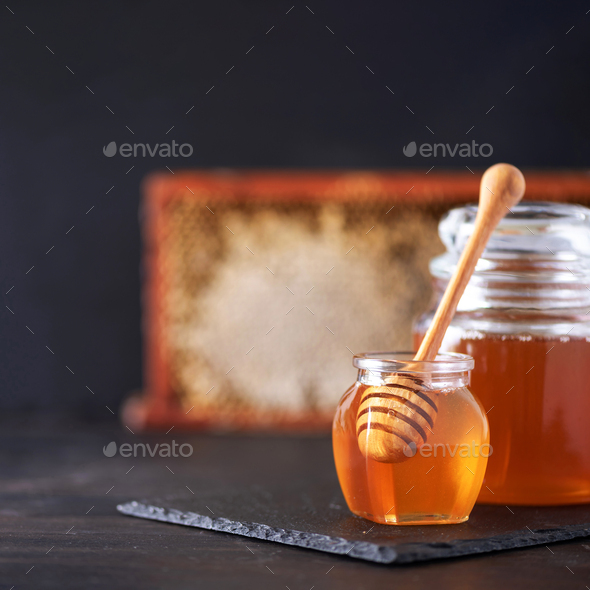 Honey jar, honeycomb and wooden spoon in jar on black background. Copy space. Autumn harvest concept - Stock Photo - Images