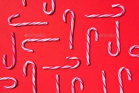 Christmas candy cane on red background. Top view. Flat lay. Creative minimal concept. Greeting card - Stock Photo - Images