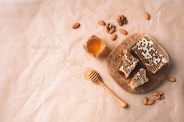 Bee pollen granules, honey jar with wooden dropper, honeycomb and almond nuts on craft paper - Stock Photo - Images