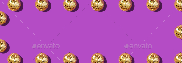 Creative Christmas pattern. Frame with shiny gold disco balls over violet background. Flat lay, top - Stock Photo - Images