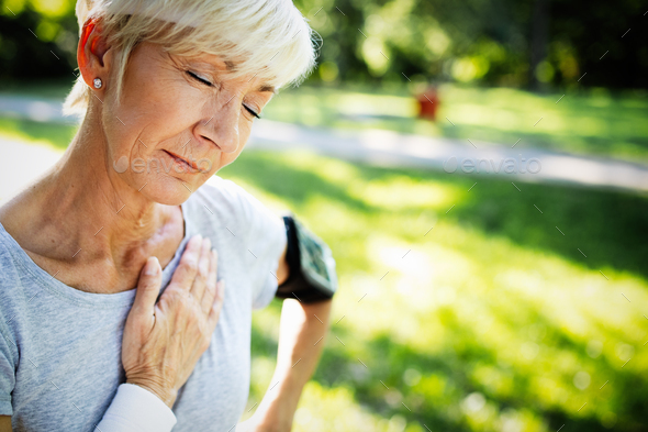 Senior woman with chest pain suffering from heart attack during jogging - Stock Photo - Images