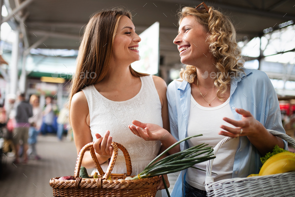 Young happy women shopping vegetables and fruits on the market - Stock Photo - Images