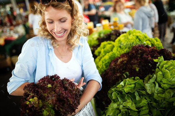 Picture of woman at marketplace buying vegetables - Stock Photo - Images
