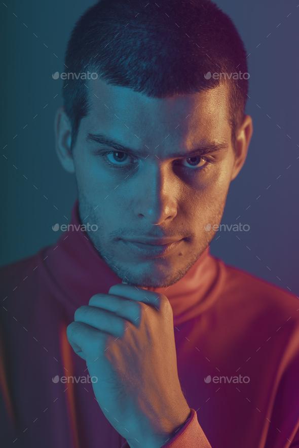 Studio close-up portrait of attractive male model. Color flash studio light - Stock Photo - Images